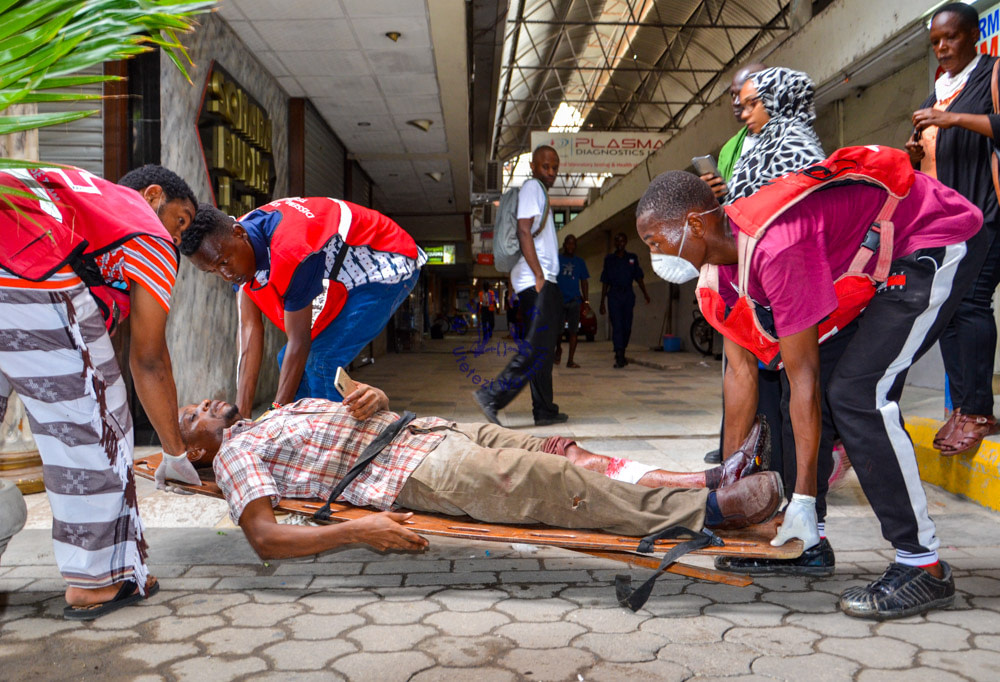 Kenya Red Cross personnel assist a local police brutalized at the Likoni crossing channel on March 27, 2020.