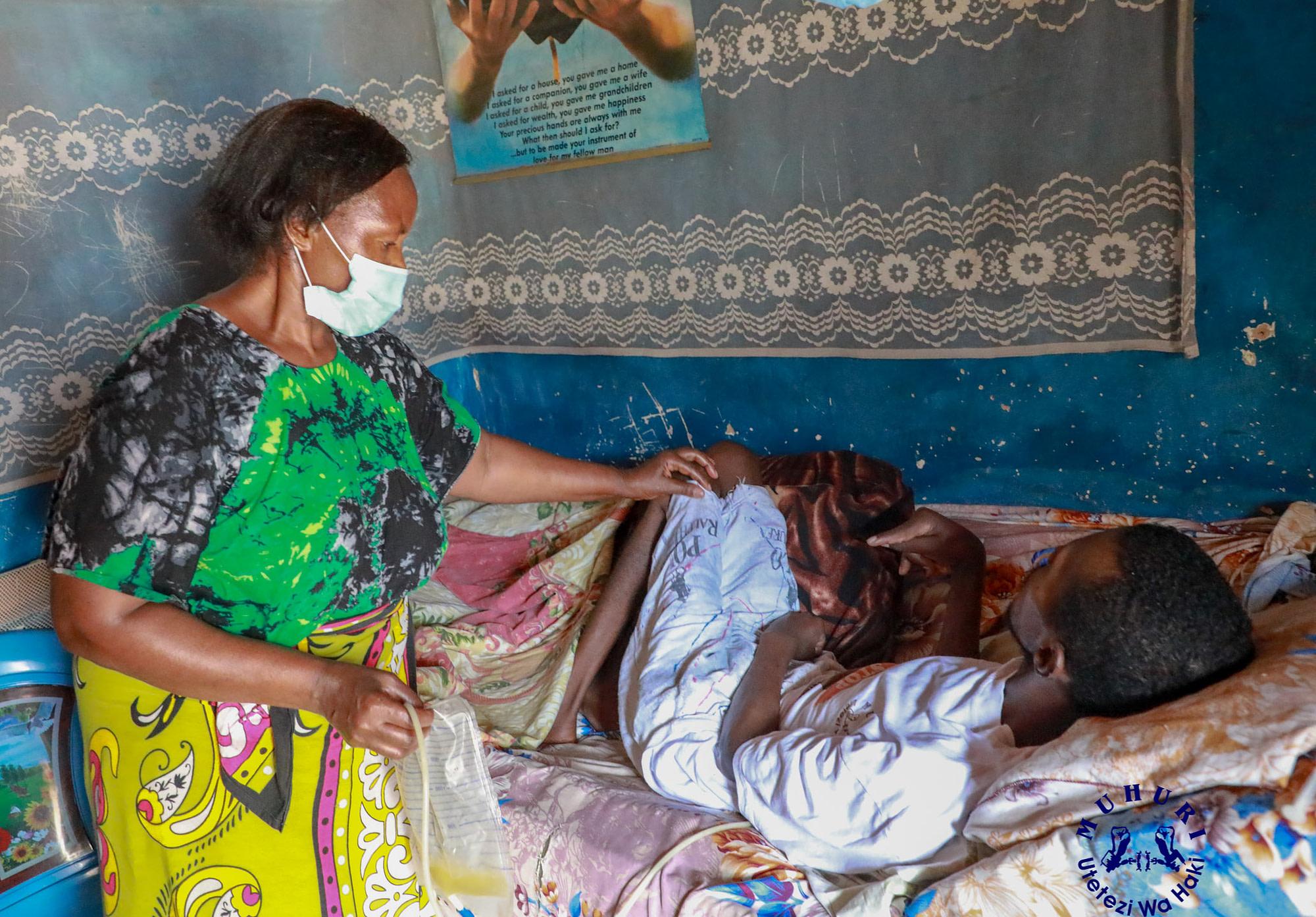 Rose Waruguru with her comatose son, Joseph Macharia. Police brutalized him. Photo: Ernest Cornel.